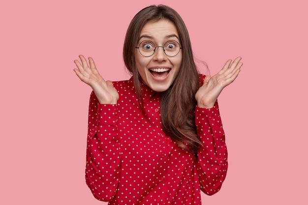 Foto interna de uma mulher morena positiva com uma camisa de bolinhas vermelhas, mantém as mãos perto do rosto, sente-se feliz, tem uma expressão facial radiante, modelos sobre um fundo rosa