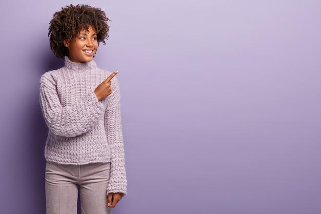 Foto interna de uma mulher negra de aparência agradável com cabelo encaracolado, aponta no canto superior direito, feliz em mostrar algo à venda na loja, vestida com roupas violetas de um tom. promoção