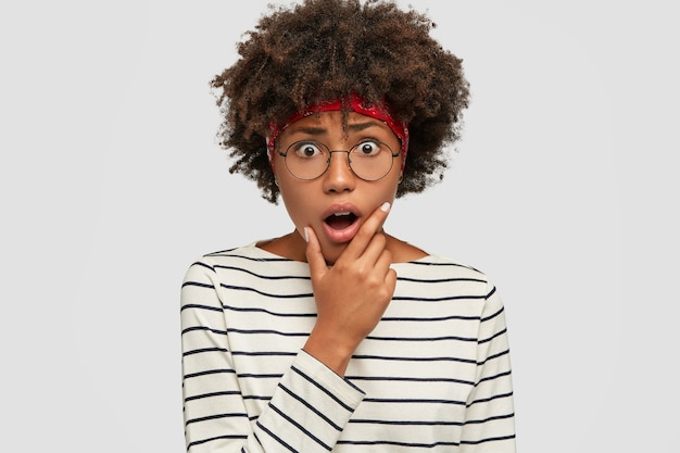 Foto interna de uma mulher negra estupefata mantendo o queixo caído, parecendo aterrorizado, usando roupas casuais