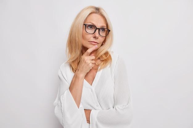 Foto interna de uma mulher pensativa de meia-idade de cabelos claros relembra algo da vida, olha para longe, mantém a mão no queixo, maquie plano usa óculos para correção da visão, blusa de seda branca elegante