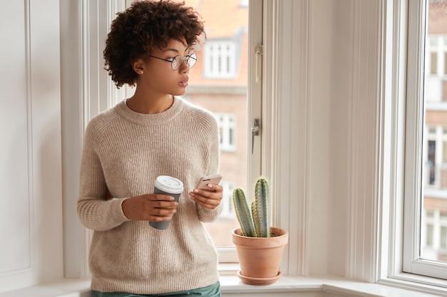 Foto interna de uma mulher pensativa de pele escura usando smartphone para comunicação online
