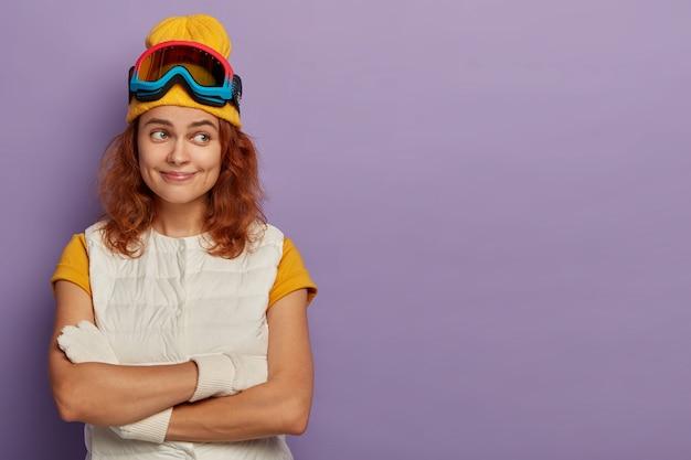 Foto interna de uma mulher ruiva feliz com as mãos cruzadas, usando chapéu amarelo e colete branco, encostada na parede roxa, copie o espaço