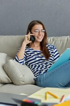 Foto interna de uma mulher satisfeita conversando ao telefone enquanto está sentada em um sofá confortável, discute relatório financeiro, usa macacão de marinheiro, jeans e óculos, sorri feliz, gosta do trabalho remoto