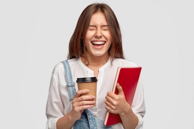 Foto interna de uma mulher satisfeita e alegre rindo positivamente, mantendo os olhos fechados, vestida com roupas elegantes
