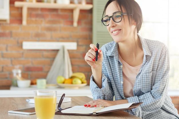 Foto interna de uma mulher sorridente e feliz sentada à mesa da cozinha, fazendo anotações no diário, planejando o que fazer,