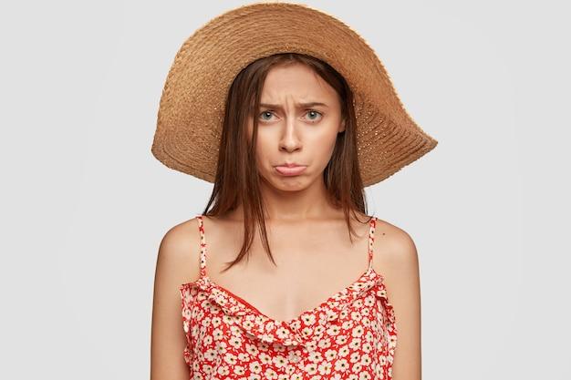 Foto interna de uma mulher triste e ofendida com chapéu de verão e vestido vermelho