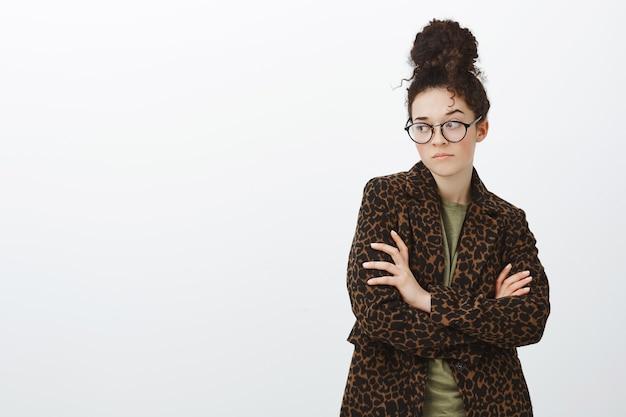 Foto interna de uma namorada na moda, ciumenta e chateada, usando óculos pretos e casaco de leopardo sobre uma camiseta, cruzando as mãos no peito e olhando para a esquerda com uma expressão incomodada e ofendida
