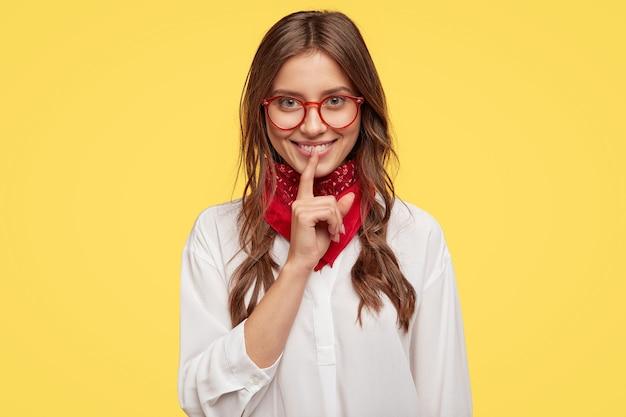 Foto interna de uma senhora alegre e satisfeita com o cabelo penteado levemente, mantendo o dedo indicador sobre a boca