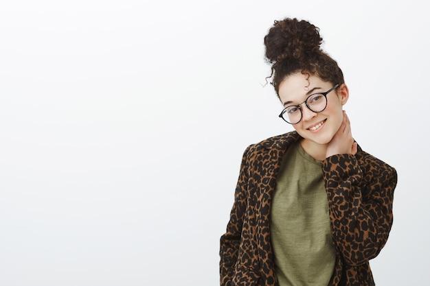 Foto interna de uma tímida namorada tímida de óculos pretos com penteado coque, tocando o pescoço e inclinando a cabeça com um lindo sorriso sedutor