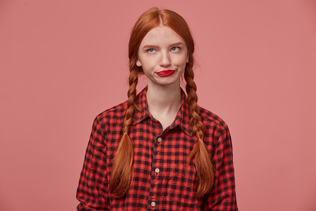 Foto interna de uma triste fêmea de gengibre negativo, pressionando os lábios, olhando de lado para o espaço da cópia com uma expressão facial confusa