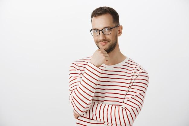 Foto interna do barman adulto fofo de óculos escuros, tocando a barba e sorrindo curiosamente