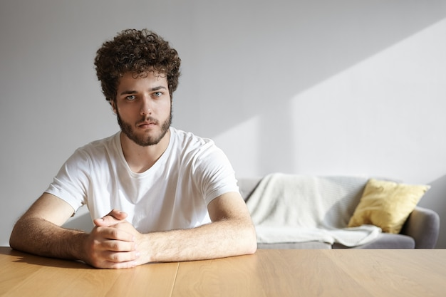 Foto interna do cara bonito e elegante jovem hippie com cabelo ondulado e barba por fazer, sentado à mesa de madeira em casa, com as mãos cruzadas e tendo uma conversa séria