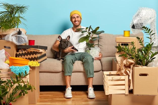 Foto interna do dono de uma casa feliz e despreocupado sentado no sofá e abraçando o animal de estimação