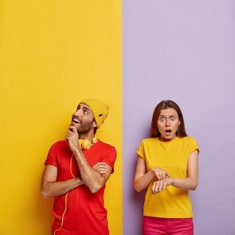 Foto interna do feliz casal da geração do milênio posando contra a parede de duas cores