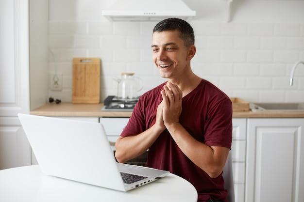 Foto interna do freelancer de homem bonito extremamente feliz, trabalhando online em casa na cozinha, tendo ótimas notícias do empregador, batendo palmas, comemorando seu sucesso, vestindo roupas casuais.