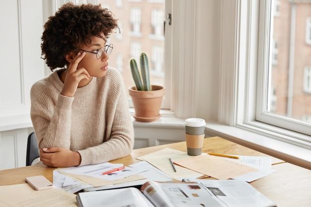Foto interna do jovem designer pensativo trabalhando em casa