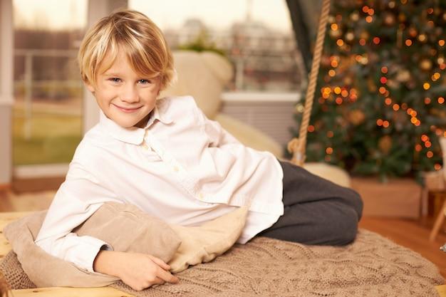 Foto interna do lindo menino fofo de dez anos com um corte de cabelo elegante e sorriso alegre, posando no travesseiro, deitado no chão em frente a árvore de natal decorada com brinquedos e festão. infância e feriados