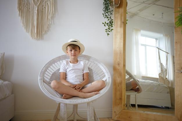 Foto interna do menino de 10 anos sentado em uma poltrona redonda, mantendo as pernas cruzadas, olhando e sorrindo para a câmera, vestindo camiseta branca e chapéu de verão. garoto bonito do sexo masculino posando no quarto com um espelho grande