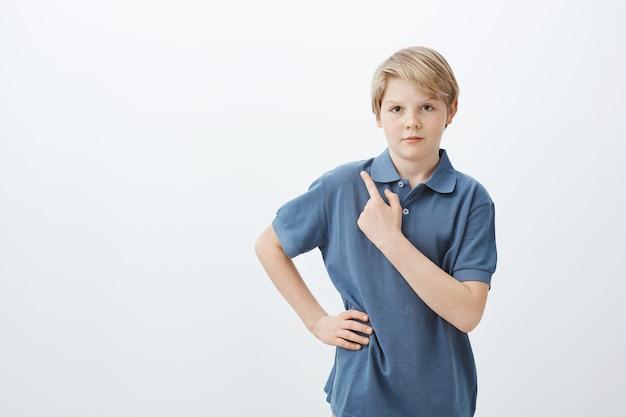 Foto interna do menino sério e fofo com cabelo loiro em uma camiseta azul, segurando a mão no quadril e apontando para o canto superior esquerdo com o dedo indicador
