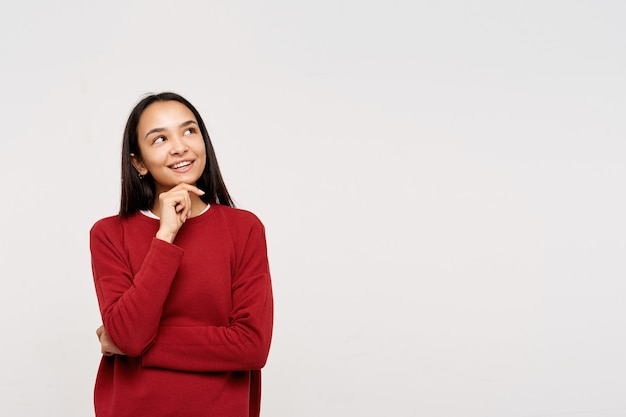 Foto interna jovem satisfeita morena de cabelos compridos vestida com um moletom vermelho, apoiando o queixo na mão levantada e olhando alegremente para cima, posando sobre uma parede branca