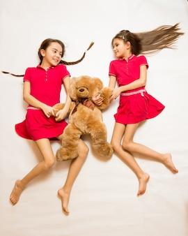 Foto isolada da vista superior de duas irmãs deitadas no chão brincando com o ursinho de pelúcia
