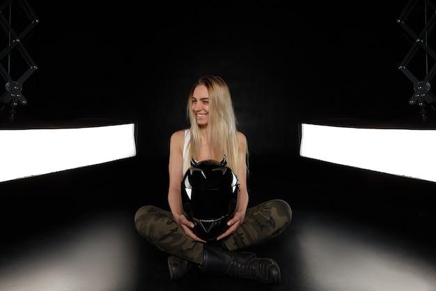 Foto isolada de alegre e extrema jovem loira dublê ou motociclista vestindo camiseta branca e calça cáqui, sentada no chão e sorrindo feliz, segurando um capacete preto de segurança