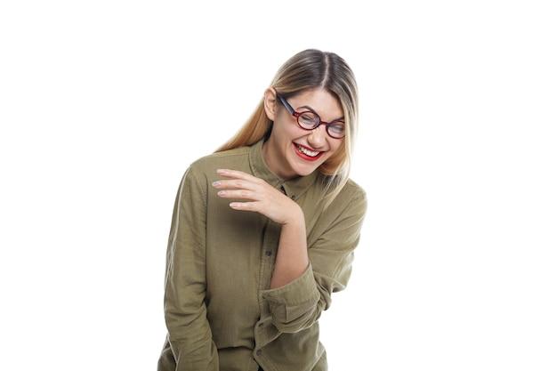 Foto isolada de alegre emocional linda garota hispter rindo alto de uma piada engraçada enquanto assiste a uma comédia em casa, fechando os olhos, inclinando-se para frente e tremendo por causa de uma risada histérica