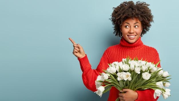 Foto isolada de alegre senhora afro-americana com cabelo crespo sorri positivamente, aponta para o lado com o dedo indicador, usa um macacão vermelho casual, carrega tulipas brancas, mostra o lugar onde comprar flores.