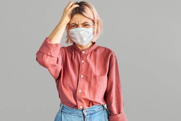 Foto isolada de aluna com cabelo rosado tendo olhar frustrado usando máscara facial em local público lotado durante o surto de coronavírus e gripe. conceito de vírus, doença, prevenção e proteção