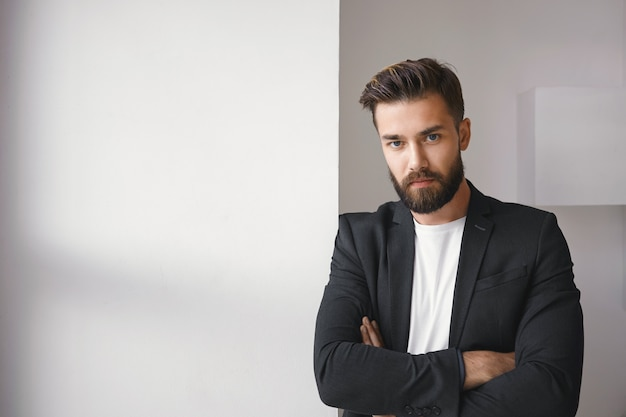 Foto isolada de atraente jovem morena barbudo empresário de sucesso vestindo uma jaqueta da moda sobre uma camiseta branca casual, mantendo os braços cruzados, expressando relutância ou desacordo
