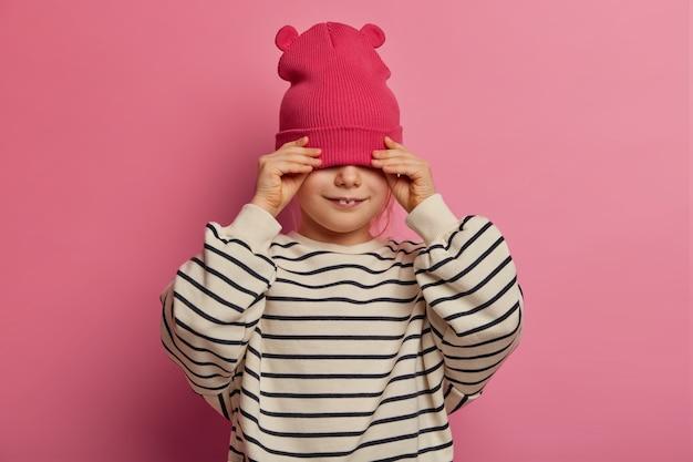 Foto isolada de criança feliz do sexo feminino mostra dois dentes, esconde os olhos com um chapéu estiloso, usa um macacão listrado casual, brinca, sendo apenas feliz, isolado na parede rosa. conceito de moda infantil.