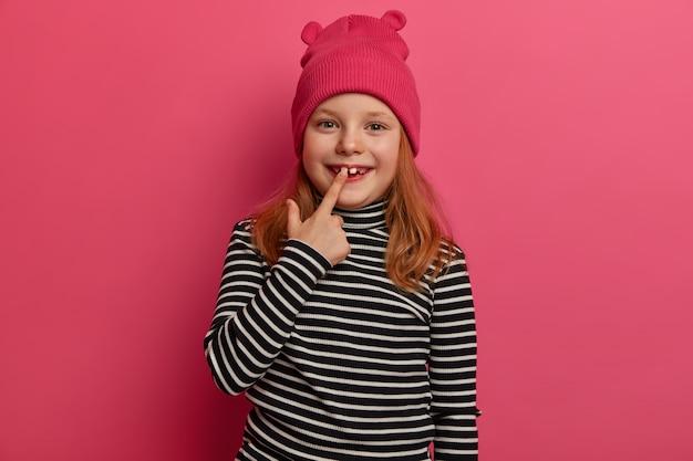Foto isolada de criança pequena se alegra com o novo dente adulto, tem cabelo ruivo, vestido com um suéter listrado e um chapéu elegante, tem poses de expressão positiva encantadoras sobre uma parede rosada. olha meus dentes brancos