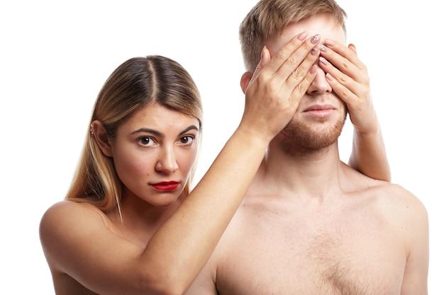 Foto isolada de dois amantes posando nus: mulher loira atraente com pele lisa bronzeada e piercing facial cobrindo os olhos de seu namorado barbudo e olhando com ar tímido