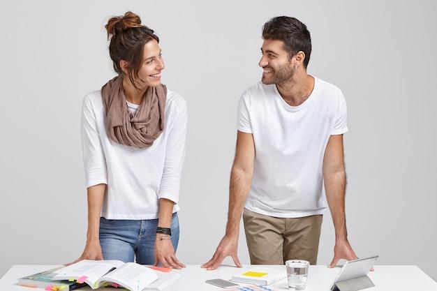 Foto isolada de dois jovens colegas de trabalho estudando literatura, preparando o trabalho do curso juntos, parando perto de uma mesa branca, vestindo roupas elegantes, ficando em casa, usando um tablet e internet sem fio para trabalhar