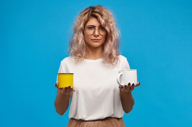 Foto isolada de duvidosa incerta jovem atraente usando roupas elegantes, segurando uma xícara branca de chocolate quente ou chocolate quente e uma caneca amarela com leite morno, hesitando
