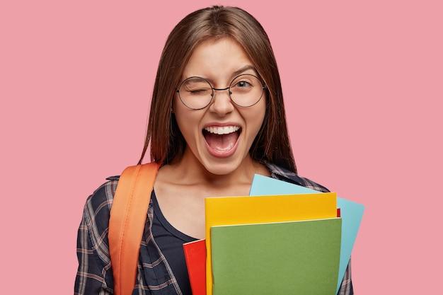 Foto isolada de estudante otimista posando contra a parede rosa com óculos
