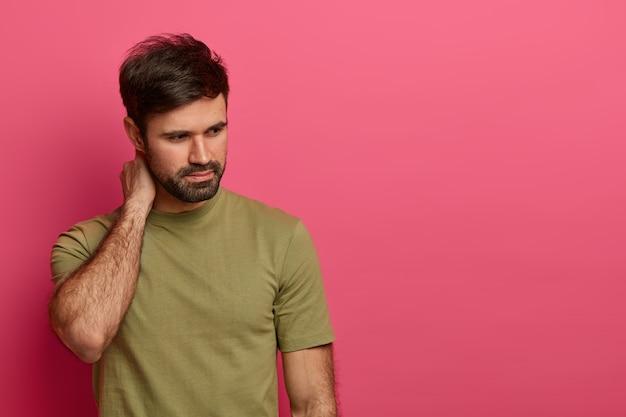 Foto isolada de homem barbudo tocando o pescoço, concentrada pensativamente para baixo