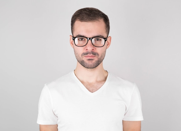 Foto isolada de jovem homem bonito com barba, bigode e penteado da moda, usa um suéter cinza casual, tem uma expressão séria enquanto ouve o interlocutor, posa em estúdio contra um fundo branco