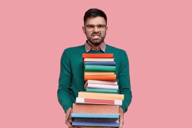 Foto isolada de jovem irritado cerrando os dentes de raiva, segura uma pilha enorme de livros, usa óculos e suéter verde, faz o dever de casa