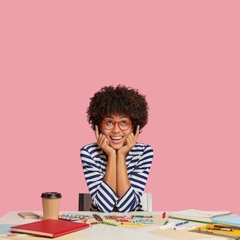 Foto isolada de jovem trabalhador criativo e alegre com penteado afro, aponta com os dois dedos indicadores para cima, sorri agradavelmente, vê algo incrível acima, mantém as mãos nas bochechas. imagem interna