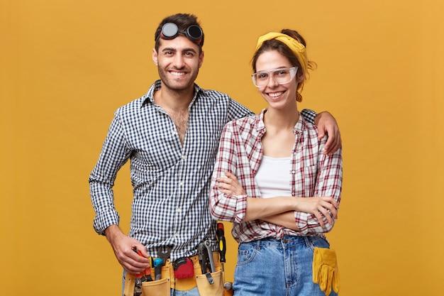 Foto isolada de jovens funcionários europeus confiantes e atraentes de manutenção, vestidos com macacões e roupas de proteção, equipados com instrumentos, prontos para o trabalho, com sorrisos felizes