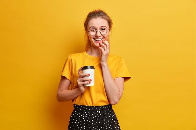 Foto isolada de menina alegre sorrindo alegremente expressa sentimentos sinceros bebe café para viagem