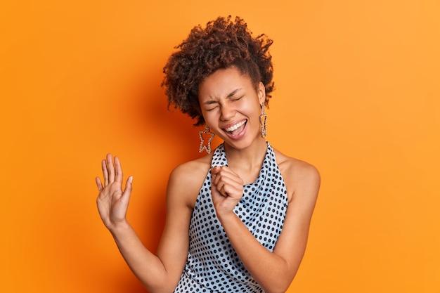 Foto isolada de mulher de cabelo encaracolado mantém a mão perto da boca fingindo cantar no microfone e usa roupas da moda mantém a palma da mão levantada isolada sobre uma parede laranja vívida