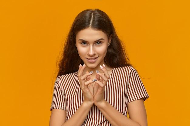 Foto isolada de mulher jovem e astuta usando um vestido estiloso com listras verticais de mãos dadas