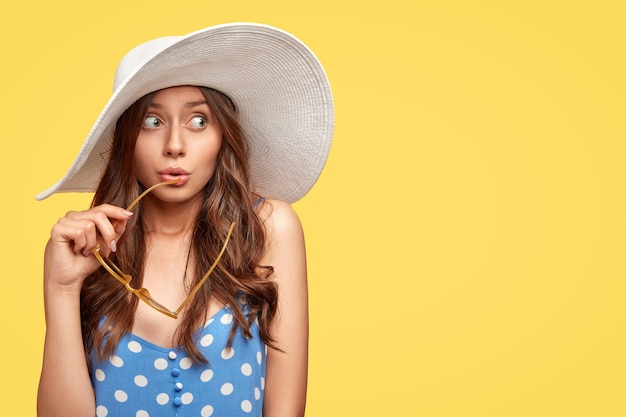 Foto isolada de mulher jovem e elegante com um chapéu, posando contra a parede amarela