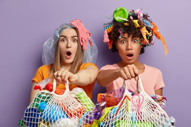 Foto isolada de mulheres multiétnicas atordoadas olhando com olhos arregalados e surpresas, segurando sacos de rede cheios de lixo plástico, indo para reciclar lixo reutilizável, perto da parede roxa