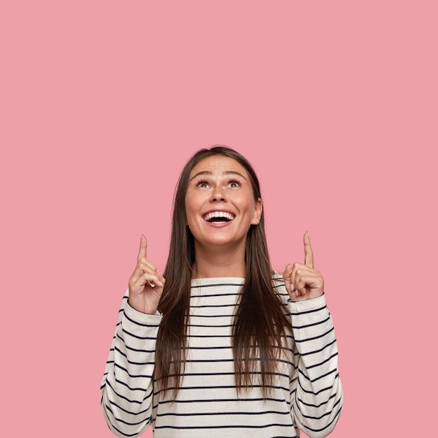 Foto isolada de namorada feliz em alto astral, apontando com os dois dedos indicadores para cima