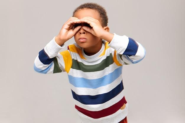 Foto isolada de um garoto afro-americano curioso fazendo gestos com as duas mãos perto dos olhos e olhando através de buracos como se estivesse usando binóculos, procurando algo à distância. conceito de infância e diversão