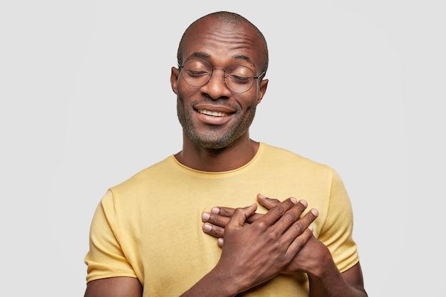 Foto isolada de um homem afro-americano encantado com uma expressão alegre