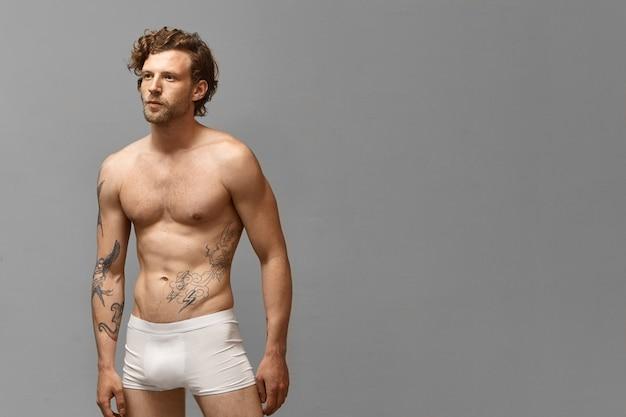 Foto isolada de um homem atlético atraente com penteado elegante e tatuagens no braço e no torso nu, vestindo apenas cuecas boxer brancas, posando para uma parede em branco com copyspace para seu anúncio